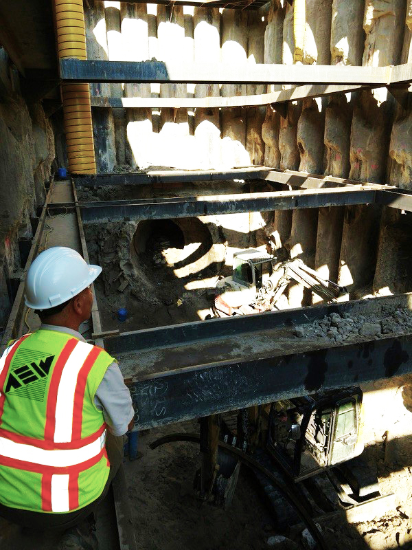 "AEW President & CEO Roy Rose inspects the recovery shaft progress from the fourth and final set of ""wales"" (horizontal I-beams) near the bottom of the excavation. Smaller excavators are at work in the bottom of the shaft clearing out the debris from the damaged pipe and surrounding soil."