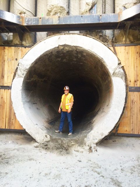 "AEW's Lead Inspector Keith Lumma in the 11-foot diameter interceptor pipe that is just east of the recovery shaft. This portion of the interceptor, including the 3,700 feet further east to Control Station No. 3, will be relined with  9' 2"" diameter HOBAS pipe to help ensure the integrity of the interceptor going forward. The bottom of the shaft is 60-feet below ground level."