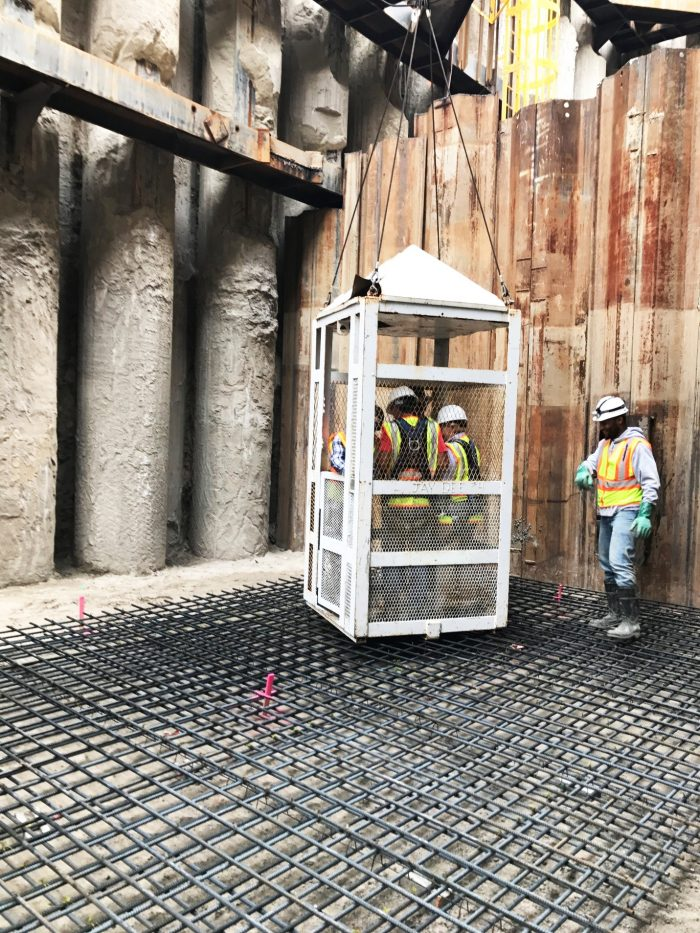 "The ""man cage,"" with Commissioner Miller and Executive Hackel, reaches the bottom of the 65-foot deep recovery shaft."