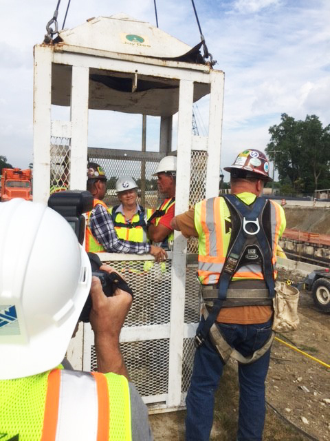 "Commissioner Miller and Executive Hackel being secured in a ""man cage"" prior to their descent into the repair site."