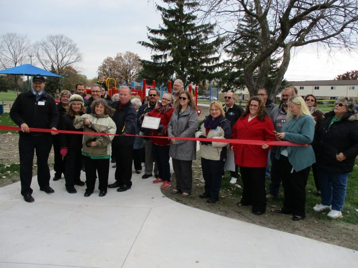 the Fraser First Booster Club and the City of Fraser held a Ribbon Cutting ceremony to celebrate the completion of the second phase of the park. Booster and city officials including Vania Apps, on the scissors, Mayor Michael Carnagie, Councilman Michael Lesich, City Manager D. Wayne O'Neal, Parks and Rec Director Christina Woods, and a number of other officials and volunteers were all on hand for the very special day.