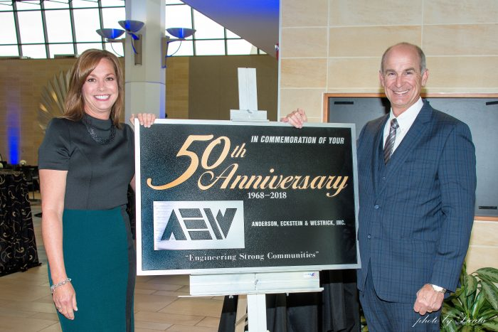 AEW's President & CEO Steve Pangori, and his wife, Laura, with the beautiful metal plaque that was gifted to AEW on their Golden Anniversary by Joseph DeFelice of J J Mich, Inc., and the Roseville Schools Board.