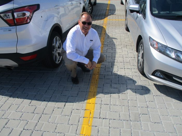 Lyle with the Permeable Brick Paver System that was installed in the parking lot.
